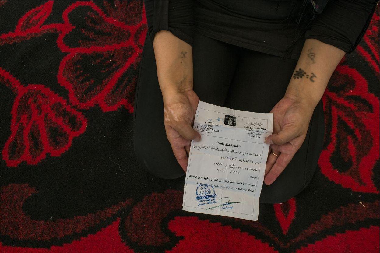 """Une femme Yazidi de 25 ans a montré son """" Certificat d'Emancipation """" que lui avait remis le Libyen qui l'avait transformée en esclave. Il expliqua qu'il avait terminé son entrainement comme kamikaze et qu'il prévoyait de se faire exploser, et donc, la libérait."""