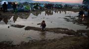 Un enfant jouant dans l'eau boueuse, à l'écart des tentes entassées dans ce no man's land.