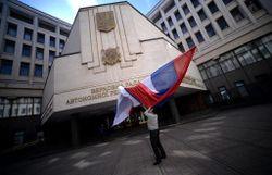 Une personne porte un drapeau russe devant le Parlement de Crimée, à Simféropol le 13 mars 2014