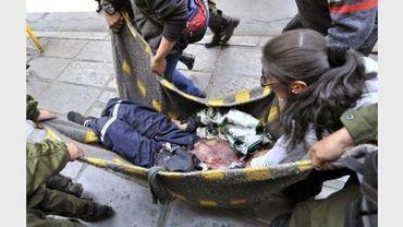Des policiers anti-émeute aident des manifestants à porter un mineur blessé par une explosion de dynamite, le 18 septembre 2012 à La Paz