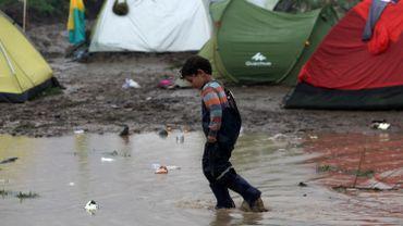 Un enfant marche dans une flaque boueuse dans un camp de fortune installé à la frontière greco-macédonienne, près du village d'Idomeni